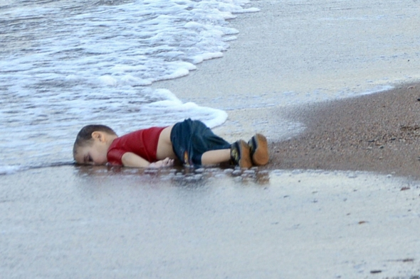 epa04910104 Washed up body of a refugee child who drowned during a failed attempt to sail to the Greek island of Kos, at the shore in the coastal town of Bodrum, Mugla city, Turkey, 02 September 2015. At least 11 Syrian migrants died in boat sank after leaving Turkey for the Greek island of Kos.  EPA/DOGAN NEWS AGENCY ATTENTION EDITORSgraphic content 